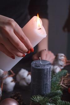 Verter cera derretida a mano de una vela blanca sobre una vela negra