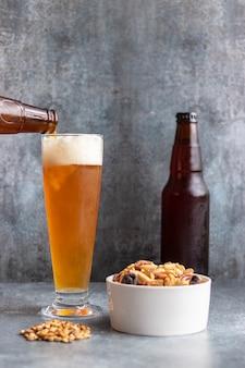 Verter la cerveza de la botella en vidrio sobre fondo gris