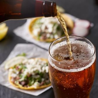 Verter cerveza frente a tacos mexicanos