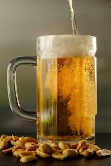 Verter cerveza fresca en un vaso con algunos cacahuetes a un lado
