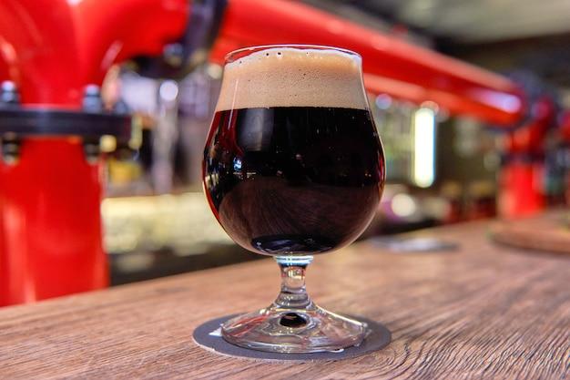 Verter cerveza de pie en la barra del bar. cerveza durk artesanal grande en grifo en menú de cafetería o pub.