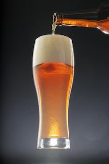 Verter la cerveza en la taza de la botella contra el fondo negro
