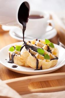 Verter chocolate sobre gofres belgas para el desayuno