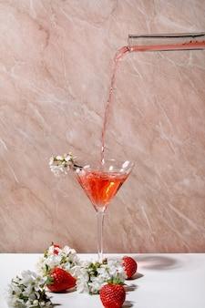 Verter un cóctel alcohólico o sin alcohol de fresa de una botella de vidrio en un vaso, decorado con ramas florecientes de cerezo sobre una pared blanca y rosa