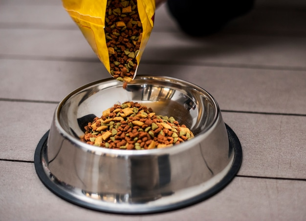 Verter comida para mascotas en un recipiente