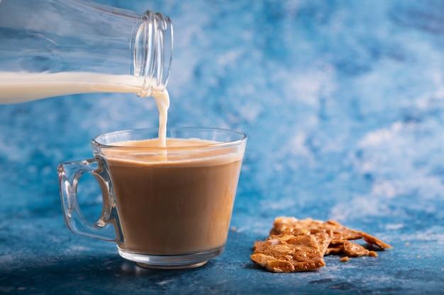Verter la leche al café sobre fondo azul.