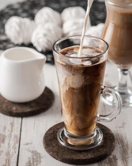 Verter la leche en la bebida de café con hielo, zephyr casero en el fondo, bodegón de desayuno dulce