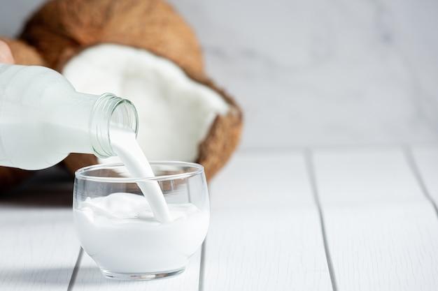 Verter la leche de coco de la botella al vaso de la mano