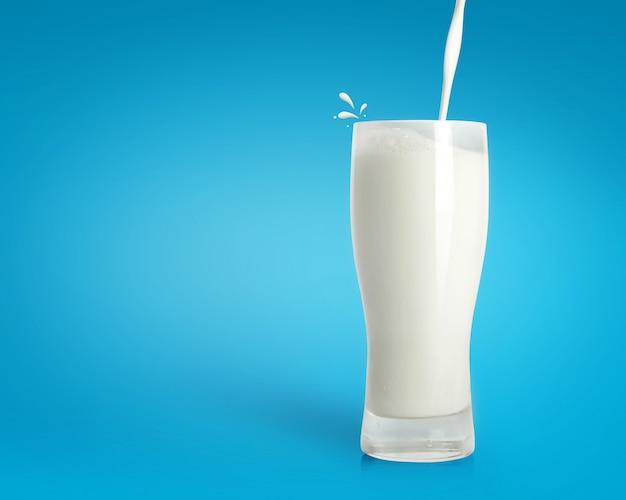 Verter la leche fresca en vidrio sobre fondo azul