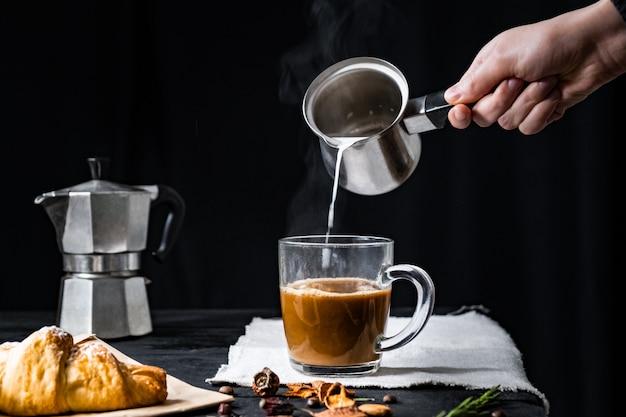 Verter leche humeante en una taza de café. agregar leche caliente al café exprés preparado en moka italiana, tiro discreto