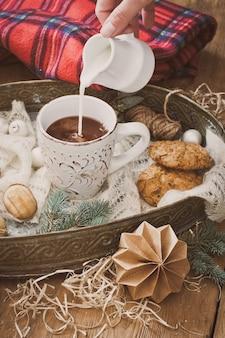Verter la leche en una taza de cacao y decoraciones navideñas.