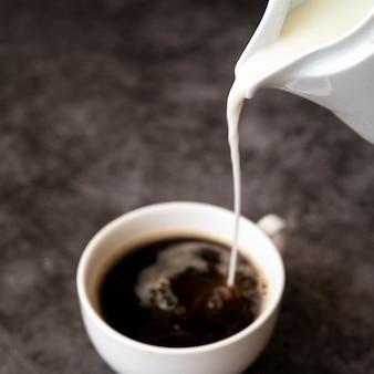 Verter la leche en una taza de café