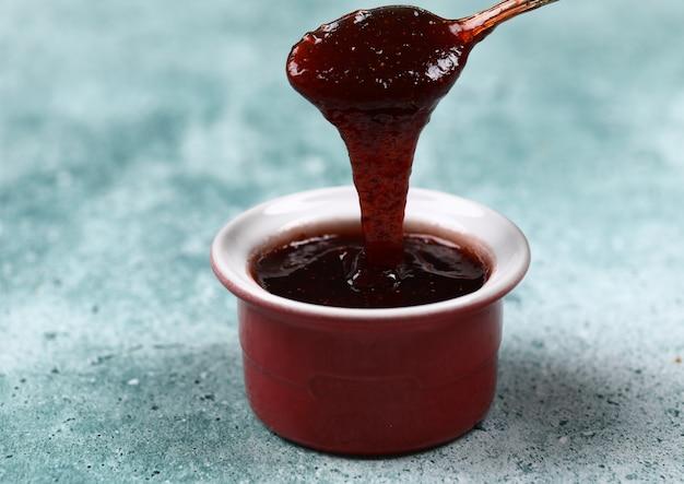 Verter mermelada de fresa en una taza roja.