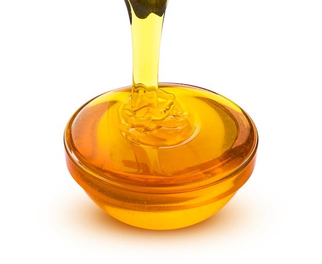 Verter la miel aislada sobre fondo blanco
