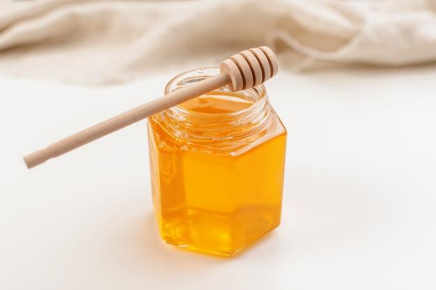 Verter la miel aromática en tarro, primer plano