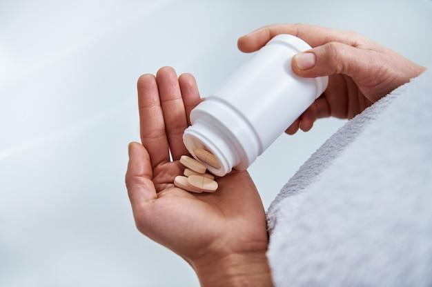Verter las pastillas de la botella blanca en el plam. concepto de medicina y salud.