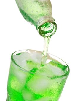Verter soda verde en vaso con hielo de botella aislado sobre fondo blanco.