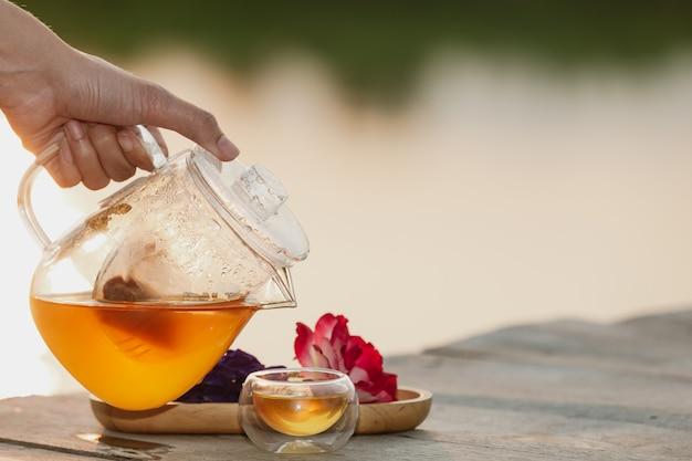 Verter té caliente en el vaso