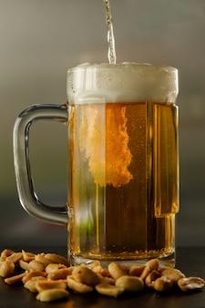Verter un vaso de cerveza con unos cacahuetes a un lado