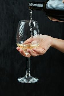 Verter vino blanco en la copa de vino sobre una superficie oscura