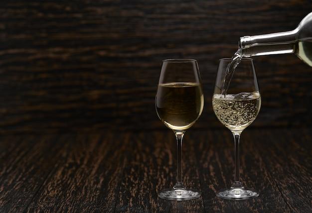 Verter vino blanco en los vasos contra la mesa de madera