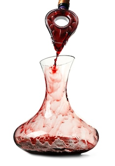 Verter el vino tinto en decantador sobre fondo blanco.