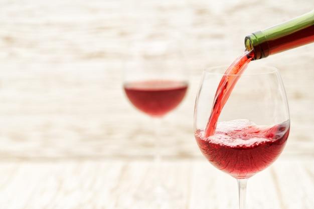 Verter vino tinto en los vasos contra la mesa de madera blanca
