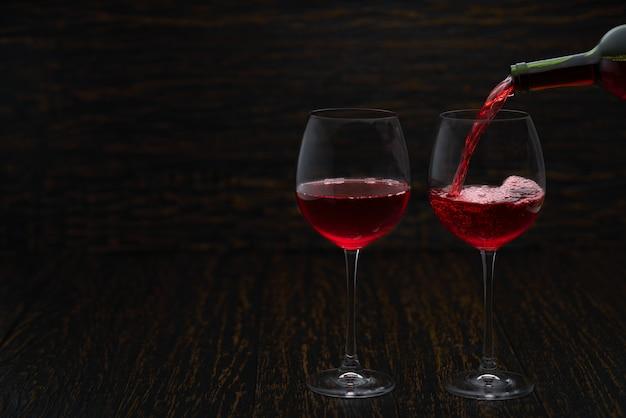 Verter vino tinto en los vasos contra la mesa de madera