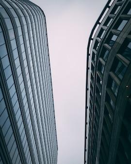 Vertical hacia arriba de modernos edificios comerciales altos con un cielo blanco