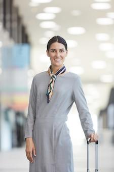 Vertical de asistente de vuelo elegante y sonriendo mientras posa con maleta en el aeropuerto