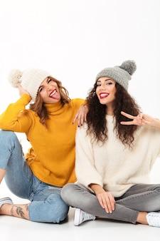Vertical dos chicas divertidas con suéteres y sombreros sentados juntos en el suelo mientras se divierten y miran la camra sobre la pared blanca