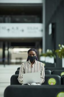 Vertical de la empresaria afroamericana con máscara mientras trabaja con un portátil en la sala de espera en el aeropuerto con distanciamiento social