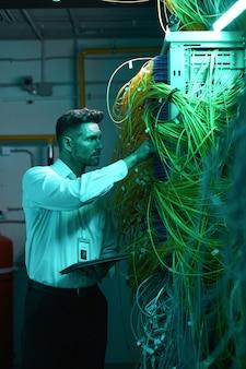 Vertical de guapo ingeniero de datos inspeccionando cables en la sala de servidores mientras trabaja con superordenador en luz azul