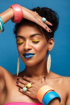 Vertical hermosa mujer afroamericana con cosméticos coloridos cerrando los ojos y gesticulando con las manos aisladas, sobre pared azul