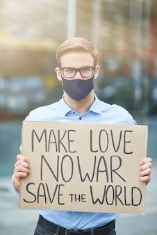 Vertical del joven activista masculino con máscara protectora negra sosteniendo pancarta o póster y mirando