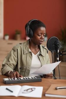 Vertical de joven afroamericana componer música y cantar al micrófono en el estudio de grabación en casa