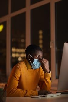Vertical del joven afroamericano con máscara en la oficina mientras usa la computadora iluminada por la pantalla