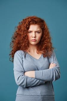 Vertical retrato de mujer gruñona estudiante con cabello rojo ondulado y pecas cruzando las manos, ofendida por sus amigos que dijeron algo grosero.