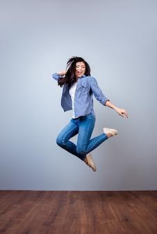 Vertical retrato de mujer joven y bonita en camisa a cuadros saltando