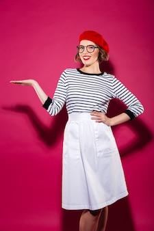 Vertical sonriente mujer de jengibre en anteojos con el brazo en la cadera con copyspace en la palma y mirando a la cámara sobre rosa