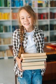 Vertical de la sonriente niña de la escuela primaria infantil sosteniendo la pila de libros en la biblioteca en