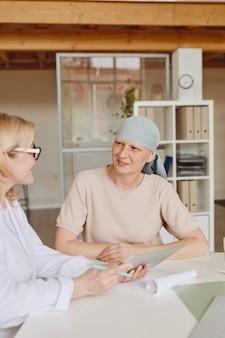 Vertical en tonos cálidos retrato de mujer calva sonriente escuchando a la doctora mostrando información en tableta digital durante la consulta sobre alopecia y recuperación del cáncer