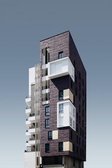 Vertical de un vidrio exótico y estructura marrón bajo el cielo azul
