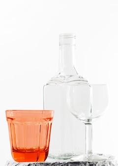 Verticales calientes de una botella vacía y vasos sobre fondo blanco.
