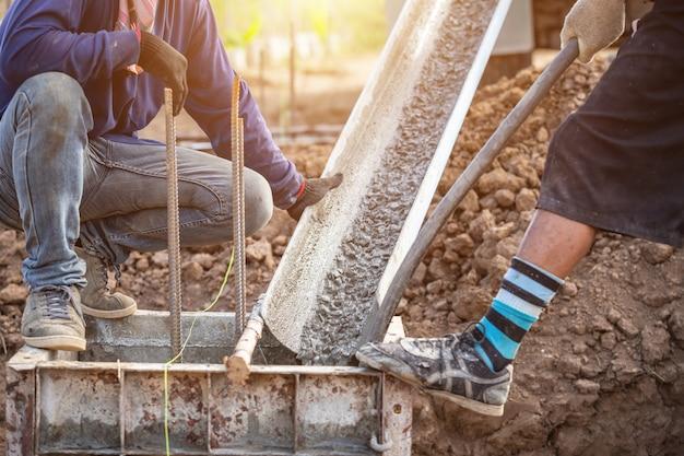 Vertido de hormigón en caja de acero para pilar de cimentación en proceso de construcción de viviendas