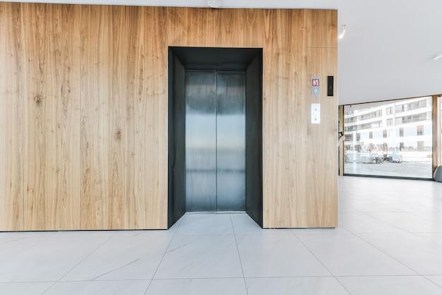 Vestíbulo de entrada del edificio de apartamentos de lujo con paneles de pared de madera y ascensor contra ventanas panorámicas