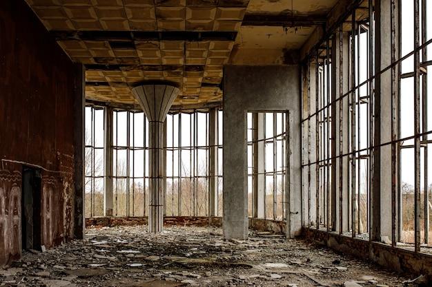 El vestíbulo en ruinas de un edificio antiguo con amplios ventanales. cristales rotos en el suelo.