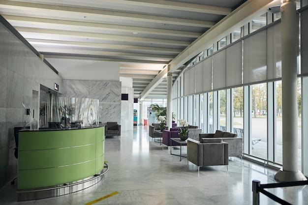 Vestíbulo con ventanas de piso a techo y muebles modernos