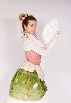 Vestida de estilo de moda del siglo xix, dama de la alta sociedad renacentista corsé y falda larga sosteniendo sun fan feliz y sonriente