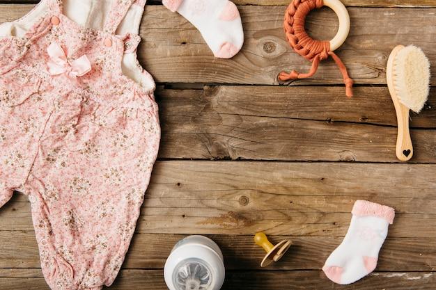 Vestido de bebe cepillo; chupete; juguete; calcetines y botella de leche en mesa de madera.